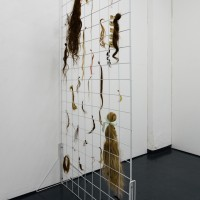 Bartered Locks, 2016. 198 x 98 cm. Hair, wax linen thread, and satin ribbon on powdercoated steel grid. Courtesy of Galería Mascota. Photo credit: PJ Rountree