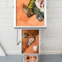 "D2GO (LP Assembly_1), 2016. Displays2Go magazine stand, pigment prints, assorted detritus. 10 x 14 x 58""."
