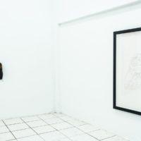 Vista de instalación: (izquierda) Angel Poyón, Día verde, 2008. Reloj y zapato. Medidas variables; (derecha) Angel Poyón, Monumentos (De la serie Área de traslado), 2006-2016. Dibujo en grafito. 66.04 x 88.9 cm. Cortesía de Km 0.2