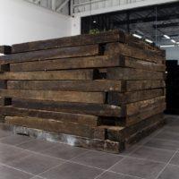 Javier Barrios y Joaquín Segura, Fortaleza, 2017. Durmientes de ferrocarril, estacas y placas de hierro, foco. Cortesía de Fundación CALOSA, Irapuato.