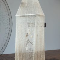 She Came From The Deep/Ella vino de lo profundo, 2017. Tar-dipped fishing net, lead weights, framed Virgin image, thread, dried vine, natural cotton balls with seeds, candle, bird's nest, dried flowers, wooden pan flute. 74 x 17 1⁄2 x 15 in. Courtesy the artist and Commonwealth and Council. Photo: Ruben Diaz.