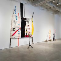 Installation view: Natalie Ball, June 12 & 13, 1872, 2015. Oil stick, marker, acrylic, graphite, charcoal, cotton, canvas, wool, lodge pole pines, coyote head & fur, bone pipes, leather, wool, brass army buttons, and wood. 96 x 120 inches; Natalie Ball, Battlefield Medicine Flags, 2015. Tanned deer hide, powwow competition number, US military jacket, wool powwow shawl, willow branches, river rocks. Dimension variable; Juan William Chavez, Potato Mound Sound, 2017. Mixed media. 120 x 108 x 48 inches. Courtesy the artist. Photo: Colin Conces