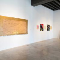 Installation view: Ronny Quevedo, The History of Rules and Measures #1, 2013. Enamel, gold leaf and contact paper on paper removed from drywall. 48 x 96 inches; Carlos Rosales-Silva, Jugos Naturales, 2015 & Puro Exitos, 2015 & Café Yucatan, 2015 & Discoteca 2000, 2015 & Nopales, 2016; Rafa Esparza, New American Landscapes. Self Portrait: Catching Feelings (Ecstatic), 2017. Wood, bailing wire, adobe (Omaha dirt, Elysian Park, Los Angeles dirt, horse dung, hay, water) scorched twigs, condom wrappers, glass chard, synthetic and agave fiber rope, dry roots, acrylic paint. 48 x 84 inches. Courtesy the artist. Photo: Colin Conces