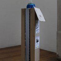 Almena (2019). Objeto escultórico: Caja de carton, tierra, musgos, palo de río y cadena. Imagen cortesía de Estudio Marte 221°